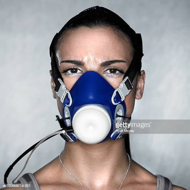 Young woman wearing oxygen mask while exercising, close-up, portrait