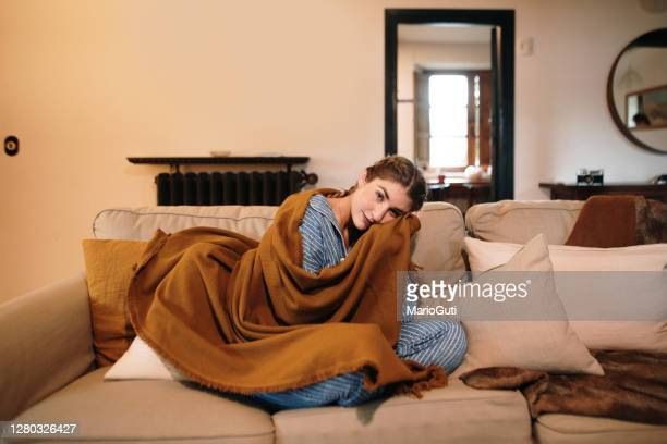 young woman wearing pajamas and a blanket sitting on sofa - warm clothing stock pictures, royalty-free photos & images