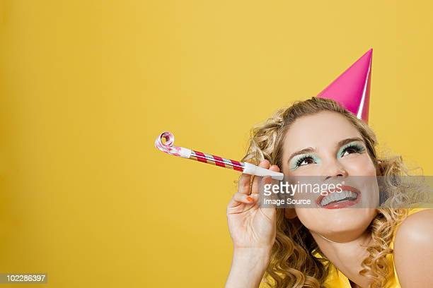 Young woman wearing party hat with party blower