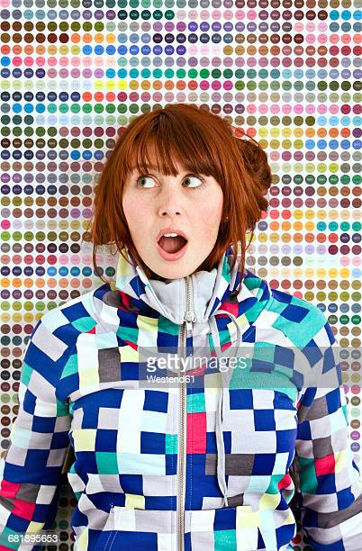 Young woman wearing patterned jacket in front of dotted wall
