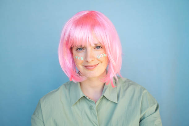 Young woman wearing pink wig, letters on her face, free doom