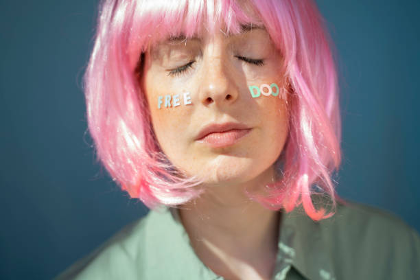 Young woman wearing pink wig, letters on her face, free doom, with eyes closed