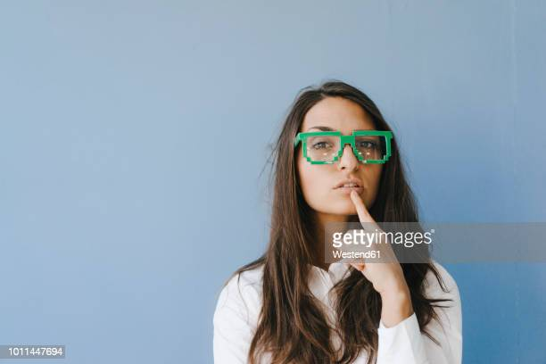 young woman wearing pixel glasses, putting finger on mouth - weisheit stock-fotos und bilder