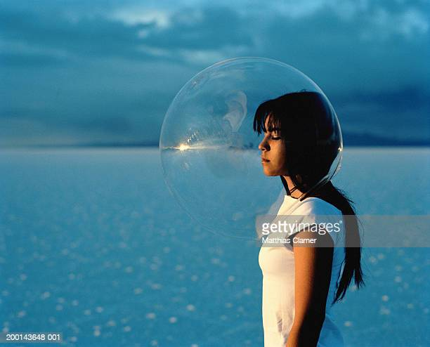 Young woman wearing protective bubble over head, side view