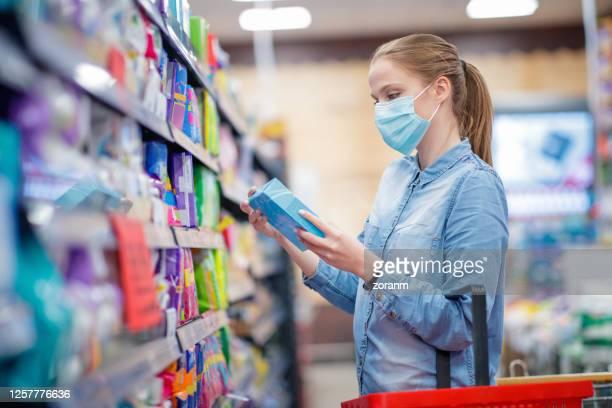 junge frau trägt schützende gesichtsmaske hält box von sanitär-pads im supermarkt - menstruation gesundheitswesen und medizin stock-fotos und bilder