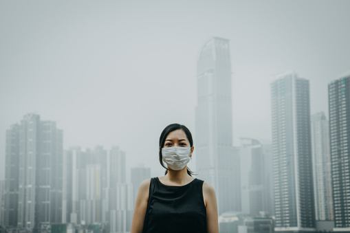 Young woman wearing protective face mask in city due to the polluted air - gettyimageskorea