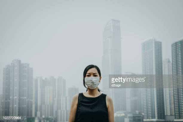 young woman wearing protective face mask in city due to the polluted air - poluição imagens e fotografias de stock