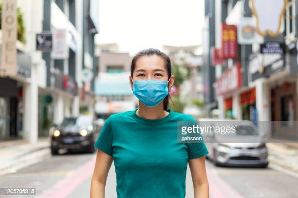 young woman wearing protective face mask in city for protection from cold and flu and viruses. - wuhan stock pictures, royalty-free photos & images