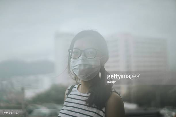 young woman wearing protective face mask outdoors due to the polluted air - smog stock pictures, royalty-free photos & images