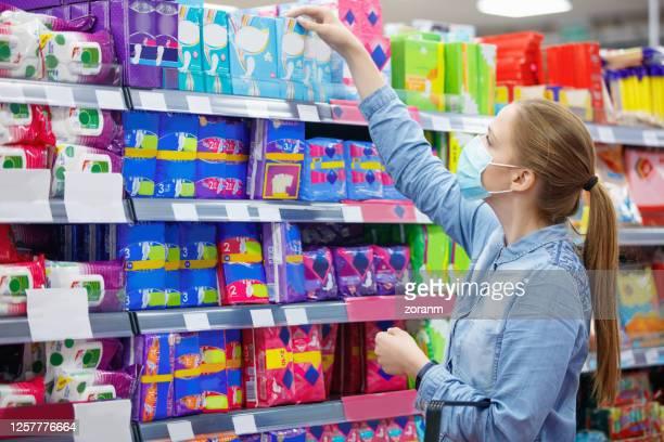 junge frau trägt schützende gesichtsmaske greift nach box von sanitär-pads im supermarkt - binden stock-fotos und bilder