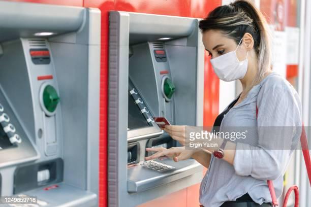 atmでお金を引き出しながら保護フェイスマスクを着用した若い女性 - 銀行 ストックフォトと画像