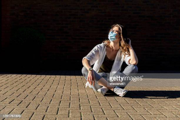 young woman wearing protective mask, sitting on ground - bronzage masque photos et images de collection