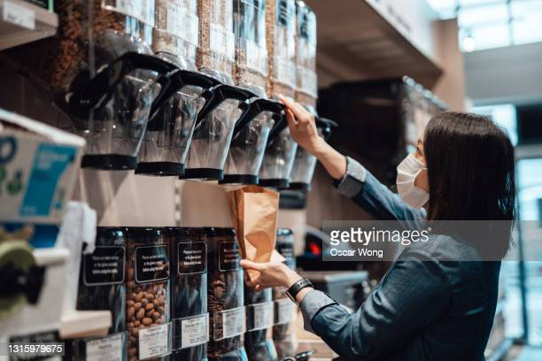 young woman wearing protective medical face mask in organic whole foods refill store dispensing seeds into paper bag. - sustainable lifestyle stock pictures, royalty-free photos & images