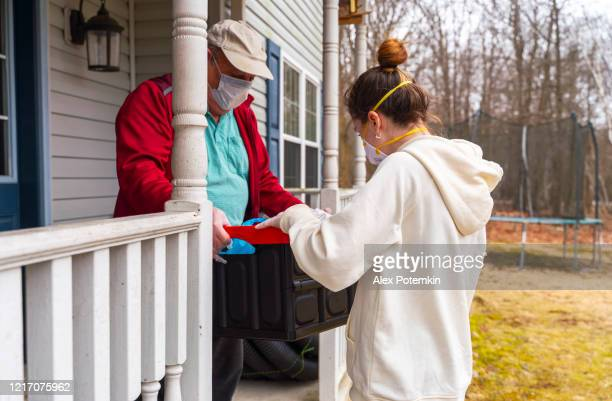 young woman wearing protective n95 mask, a courier, is delivering the groceries packed into the reusable plastic bins to a customer, a senior man, during covid-19 outbreak. - alex potemkin coronavirus stock pictures, royalty-free photos & images