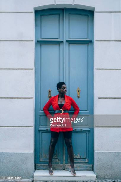 young woman wearing red blazer at blue door - blue blazer stock pictures, royalty-free photos & images