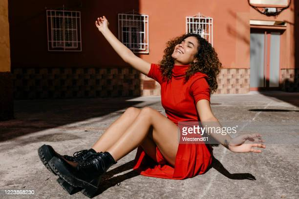 young woman wearing red dress and sitting on ground - red dress stock pictures, royalty-free photos & images