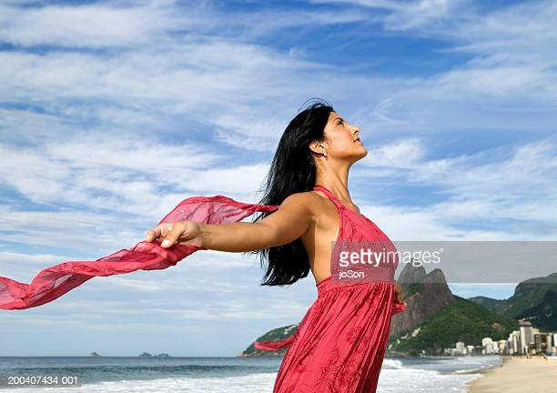 young woman wearing red dress at beach, spreading arms wide, side view - neckline stock pictures, royalty-free photos & images