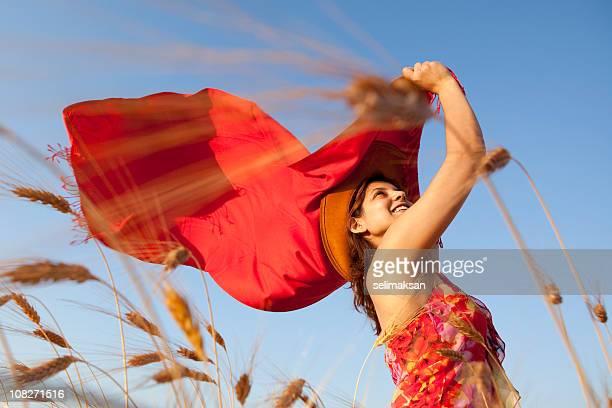 jeune femme portant robe rouge tenant écharpe rousse dans le vent - foulard accessoire vestimentaire pour le cou photos et images de collection