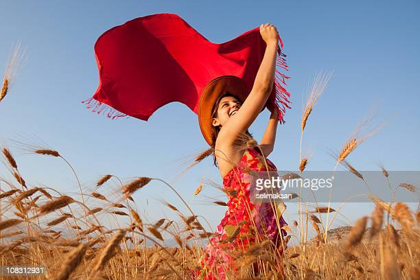 Young Woman Wearing Red Dress Holding Reddish Scarf In Wind