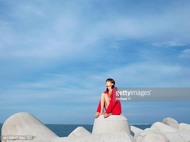 Young woman wearing red dress sitting on waterbreak