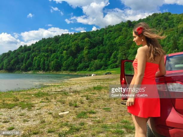 young woman wearing red dress while standing by car on field - 赤のドレス ストックフォトと画像