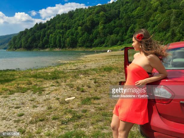 young woman wearing red dress while standing by car on field - lady madeleine stock-fotos und bilder