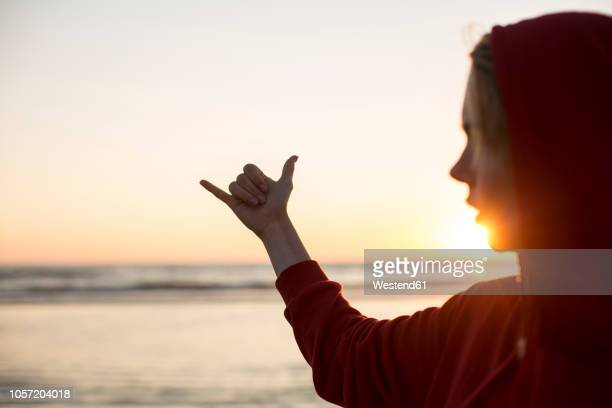 Young woman wearing red hooded jacket on the beach at sunset making hang loose gesture