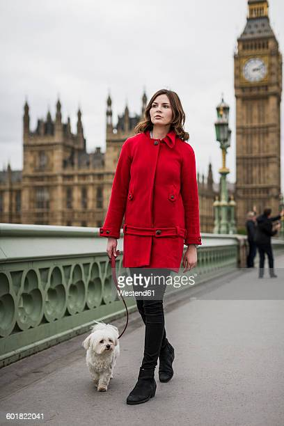 Young woman wearing red jacket going walkies with her dog