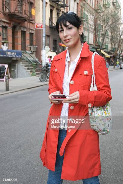 Young woman wearing red trench coat and standing on street, New York City