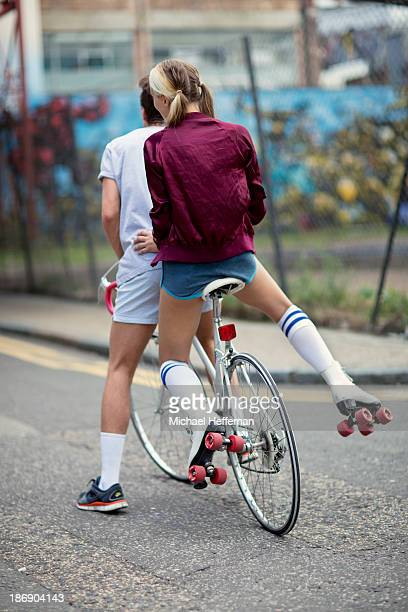 Young woman wearing rollerskates sitting on bike