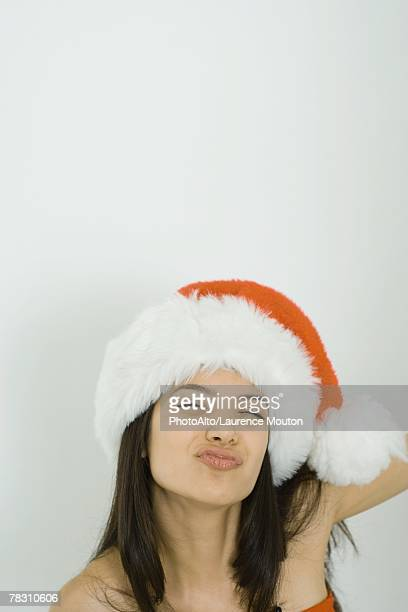 Young woman wearing Santa hat, puckering lips, squinting, portrait