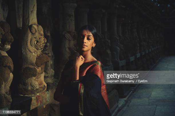 young woman wearing sari while standing by statues in temple - sari stock pictures, royalty-free photos & images