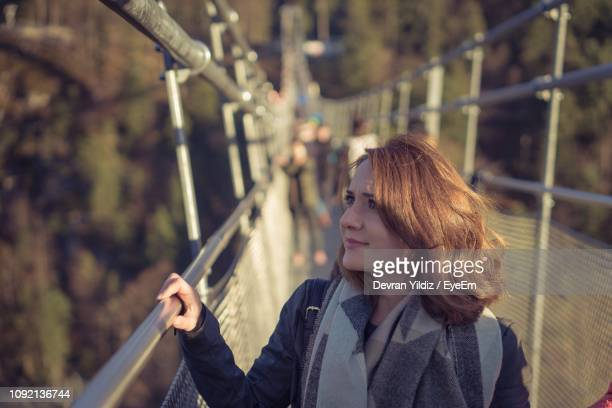 young woman wearing scarf on footbridge - neckwear stock pictures, royalty-free photos & images
