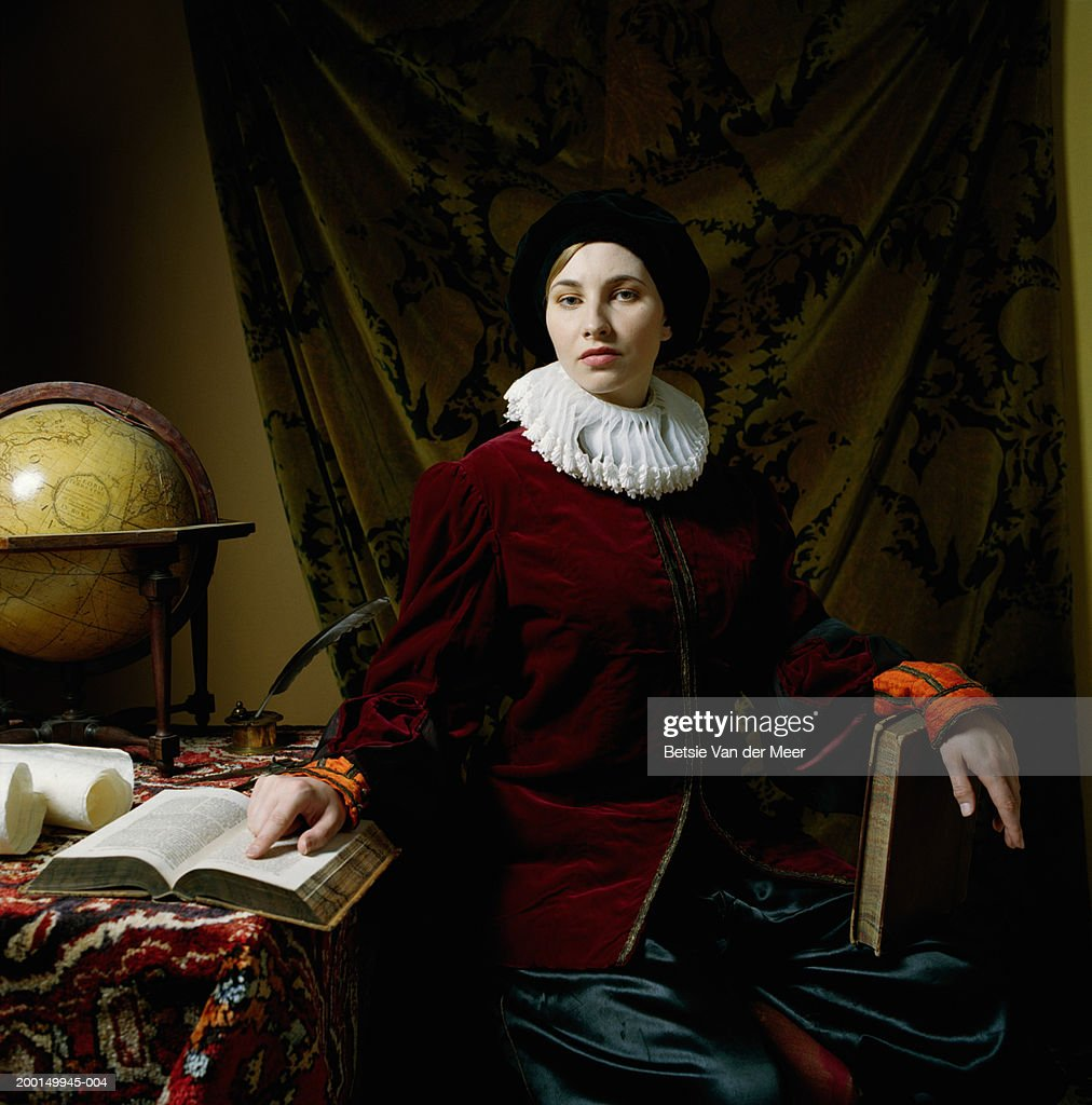 Young woman wearing scholar outfit at desk, portrait : Stock Photo