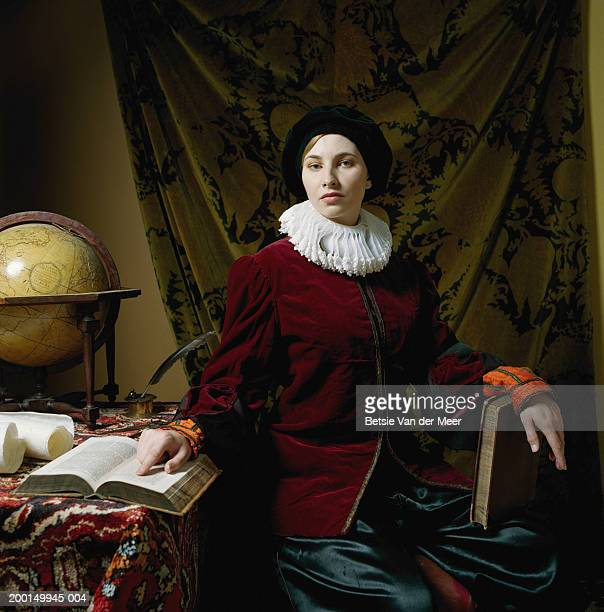 young woman wearing scholar outfit at desk, portrait - elizabethan style stock photos and pictures