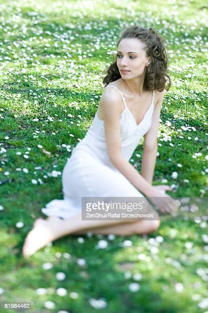 young woman wearing slip, sitting in field of flowers, looking over shoulder, smiling - frau in slip stock-fotos und bilder