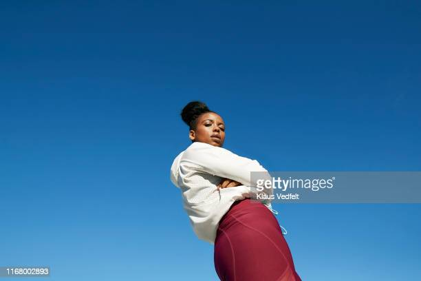 young woman wearing sports clothing against clear blue sky on sunny day - arme verschränkt stock-fotos und bilder