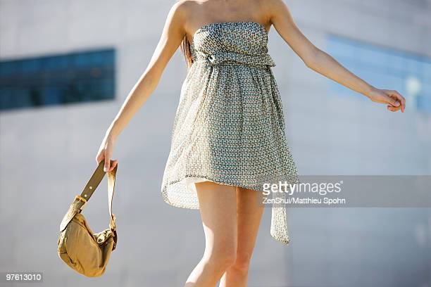 Young woman wearing strapless sundress, carrying purse, cropped