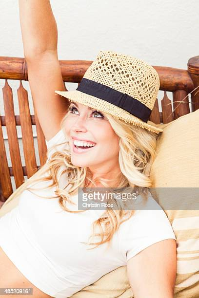 Young woman wearing straw hat looking up