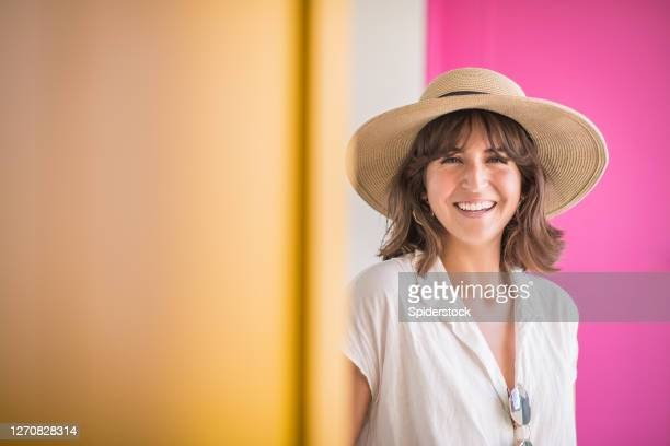 young woman wearing straw hat smiling in front of pink door - straw hat stock pictures, royalty-free photos & images