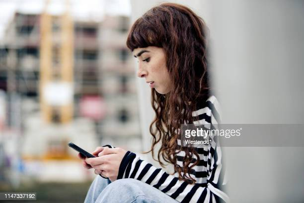 young woman wearing striped shirt, using smartphone - エッセン ストックフォトと画像