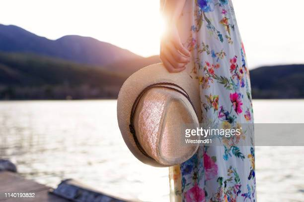 young woman wearing summer dress with floral design standing on jetty holding summer hat, partial view - サンドレス ストックフォトと画像
