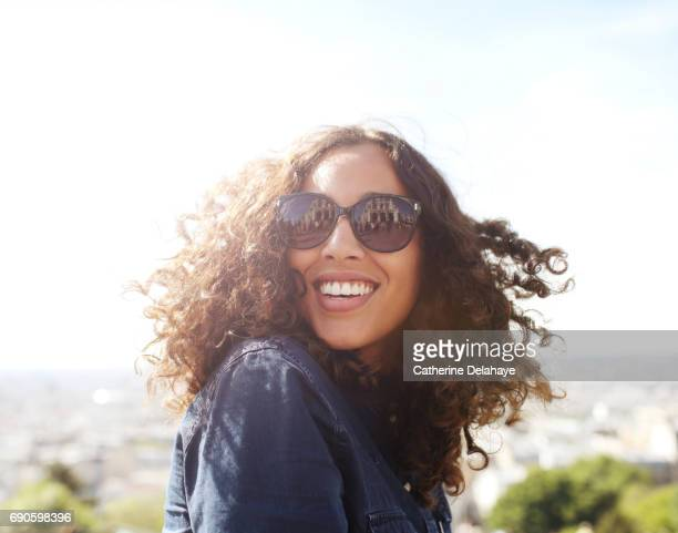 A young woman, wearing sun glasses, smiling in Paris