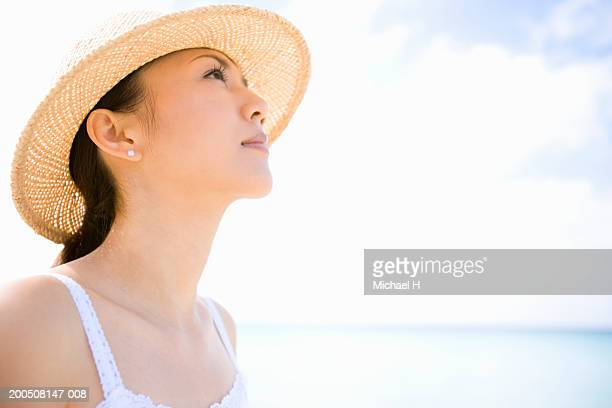 Young woman wearing sun hat on beach, looking up, side view