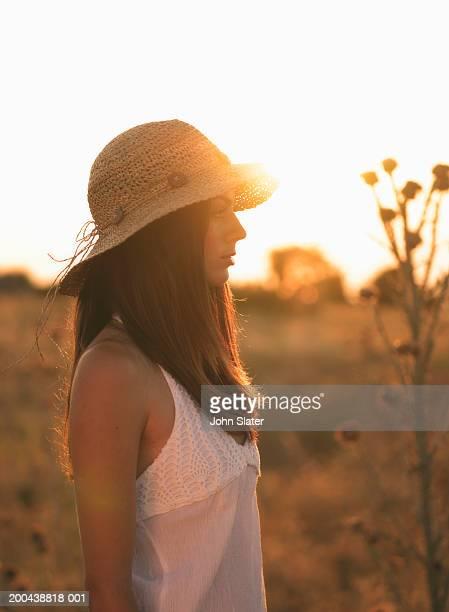 Young woman wearing sun hat, profile (sun flare)