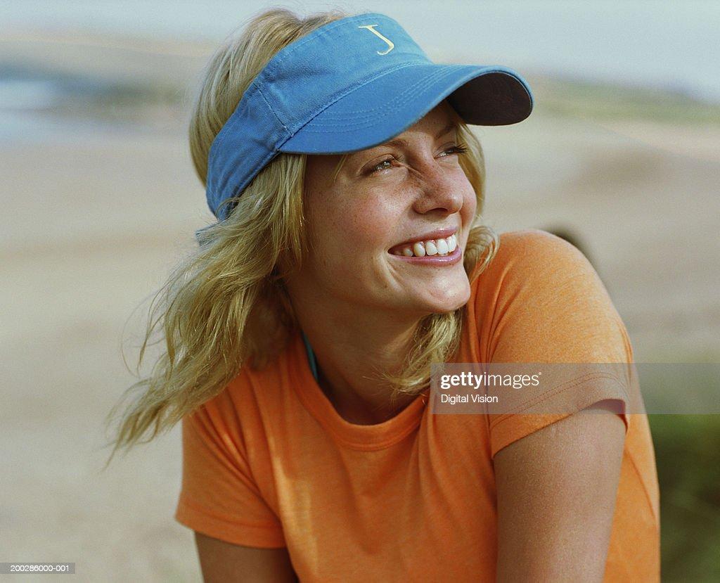 e0efa361 Young woman wearing sun visor, looking away, smiling, close-up : Stock