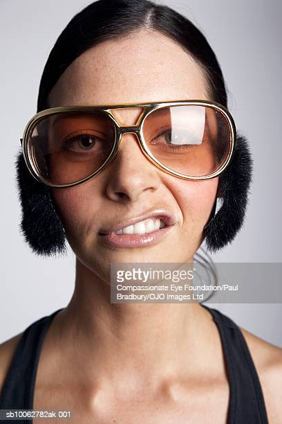 Young woman wearing sunglasses and earmuffs, pulling facial expression, portrait