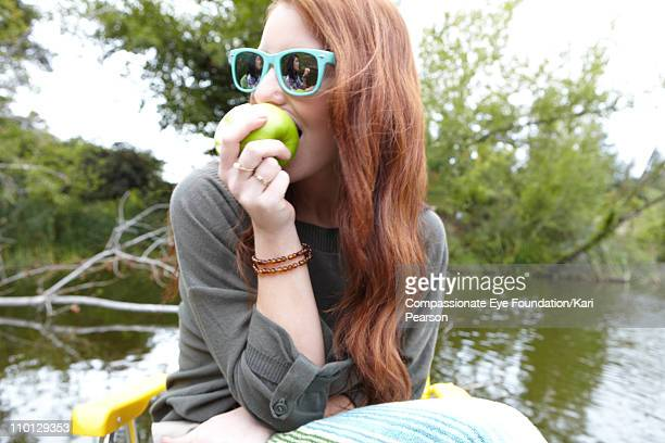 Young woman wearing sunglasses and eating an apple