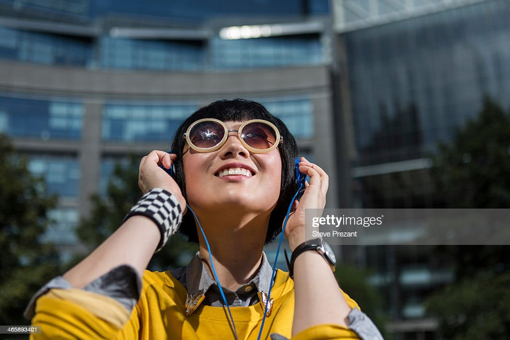 Young woman wearing sunglasses and headphones looking up : Foto de stock