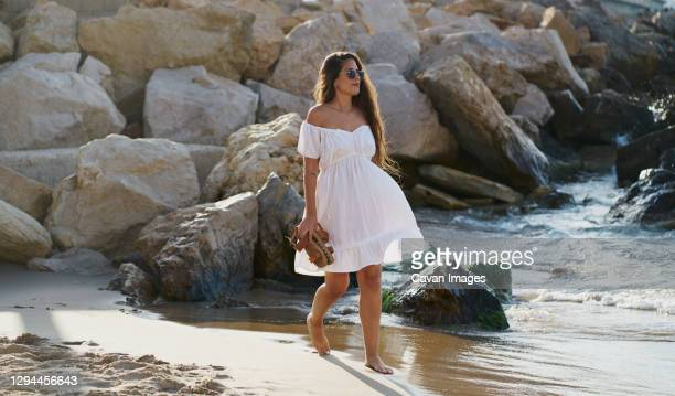 young woman wearing sunglasses and wearing a white dress walking - weißes kleid stock-fotos und bilder